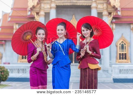Beautiful Thai Girl In Thai Costume With Umbrella,asian Woman Wearing Traditional Thai Culture Stand