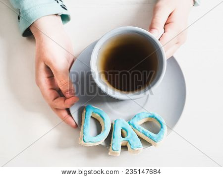 Cup Of Fragrant Tea And Biscuits In The Form Of Letters D A D In The Hands Of The Younger Daughter O