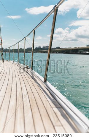 Sailing Boat Deck On A White Yacht With Teak Wooden Deck And Metal Shiny Railing In The Undulating A
