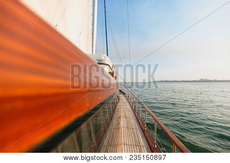 The Curtained Window On The Wooden Deck Of Brown Yacht With Wooden Rails And Golden Details In Azure