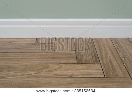 Interior Concept. Light Matte Wall, White Baseboard And Tiles Immitating Hardwood Flooring. Oak Wood
