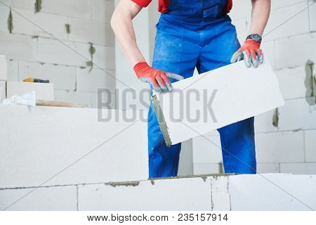 bricklayer builder working with autoclaved aerated concrete blocks. Walling poster