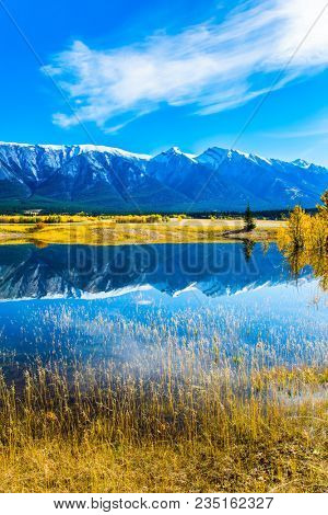 Concept of active and ecological tourism. Indian Summer in the Rockies. Rocky Mountains are reflected in the turquoise water of Lake Abraham