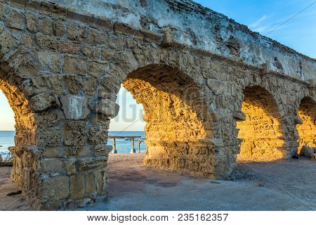 Delightful sunset on the Mediterranean coast in Israel. Well-preserved aqueduct, built in Caesarea at the beginning of the Byzantine period. Concept of ecological and historical tourism