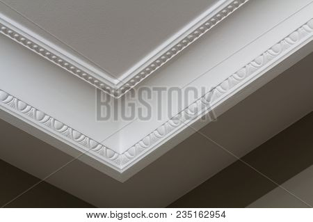 Ornamental White Molding Decor On Ceiling Of White Room Close-up Detail. Interior Renovation And Con