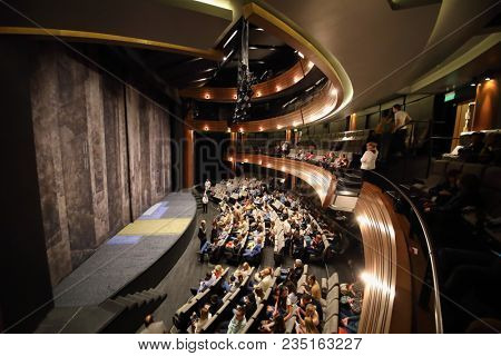 MOSCOW - SEP 14, 2017: The auditorium with a stage and a line of chairs with spectators awaiting the start of the performance in the Moscow Theater Center Cherry Orchard. View from the balcony