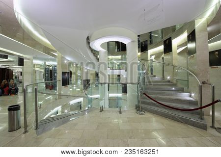MOSCOW - SEP 14, 2017: Bright foyer of the Moscow Theatrical Center with a central spiral staircase and portraits of actors who play in this theater