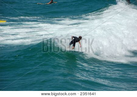 Surfer Catches A Wave.
