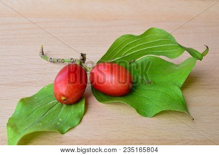 Two Fresh, Ripe Dogwood Berries With Green Leaves On Wooden Background, Close Up View