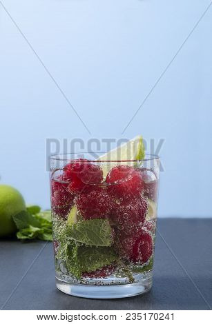 Raspberry Lemonade With Lime And Mint In A Glass. Non-alcoholic Raspberry Refreshment Drink. Raspber