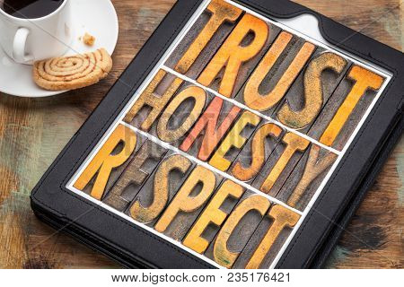 trust honesty, respect word abstract in vintage letterpress wood type on a digital tbalet with cup of coffee