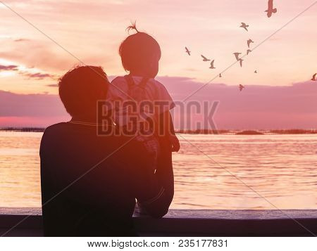 Back View Of Grandfather Carring His Niece And Looking At Seagull Birds At Sunset Beach Thailand. Si