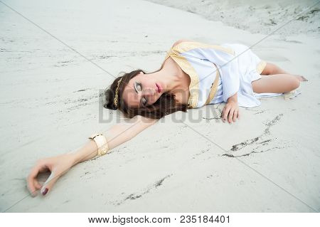Attractive Girl In Greek Tunic Lies On Sand Blindly