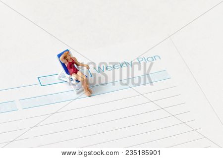 Miniature Woman Wearing Swimsuit Sitting On The Lounge Chair Next To  Weekly Planing Message On Pape