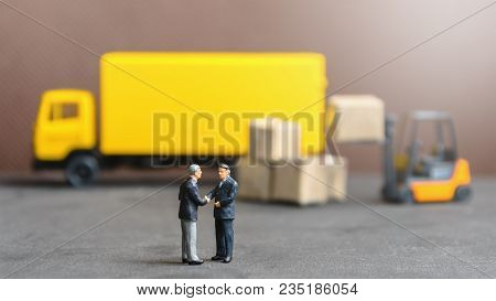 Miniature Businessman Shaking Hand With Container Truck And Carton Products Goods Box Background In