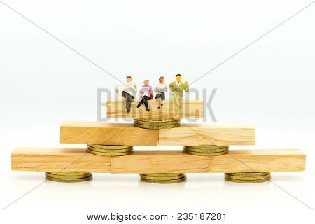 Miniature People: Businessman Sitting On A Wooden Block To Keep Money (bank). Image Use For Business