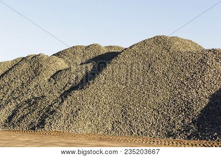 Storage Of Bulk Materials At Against A Clear Blue Sky. Supplier Of Building Materials