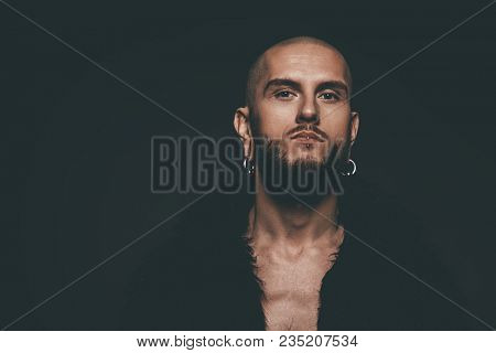 Portrait of a bearded hipster man wearing black fur coat with piercing in the ears and lips. Studio shot over dark background.