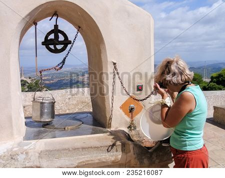 Mature Tourist Woman Travelling In Majorca Drinks Fresh Water From Old Draw Well At San Salvador Mon