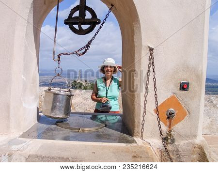 Happy Mature Tourist Woman Travelling In Majorca Stays Near Old Draw Well At San Salvador Monastery