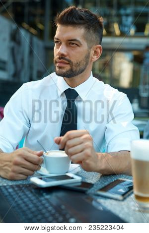 Portrait of confident businessman drinking espresso and using laptop at sidewalk cafe.