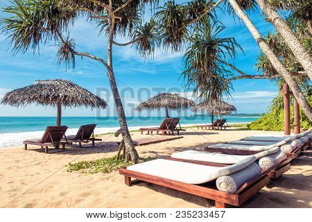 Beach Beds With Umbrellas On The Tropical Sunny Beach In Sri Lanka. Scenic Idyllic View Of A Sand Be