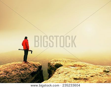 Photographer Working With Mirror Camera And Tripod On Peak Of Rock. Dreamy Foggy Landscape Misty Aut