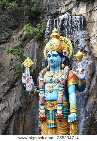 Statue of hindu god Krishna next to entrance to shrine in Ramayana cave, Batu Cave, Kuala Lumpur, Malaysia