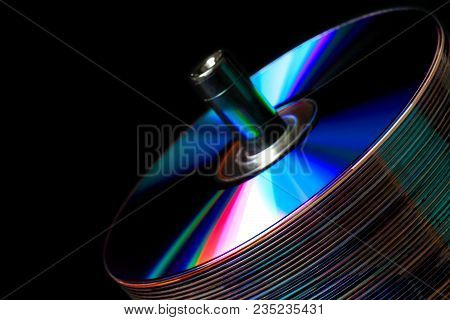 Stack Of Cds On A Dark Background With Colored Refractive Bands