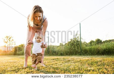 Beautiful Young Mother With Her Baby Son. First Steps.