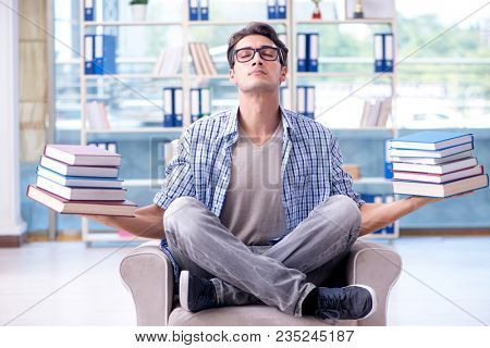 Student reading books and preparing for exams in library