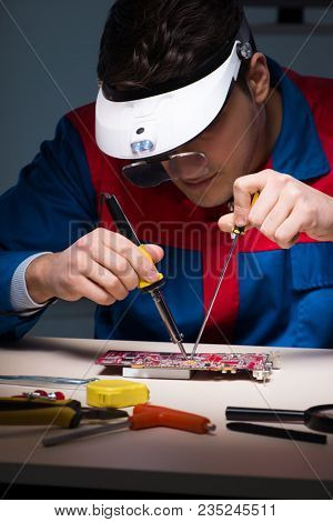 Computer specialist repairing PC late at night