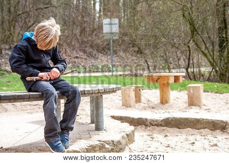 A Boy Carving And Playing With With Woodblock.