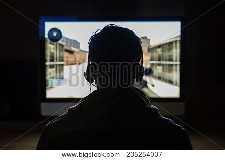 Back view of young gamer playing FPS video games at home poster
