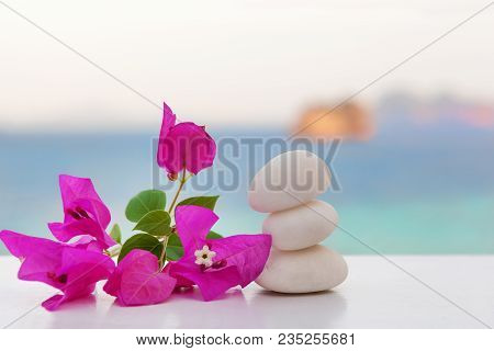 Rock Cairn With Tropical Flour, Turquise Ocean In Background.  Zen, Balance, Spa, Spirituality. Ston