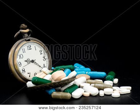Antique Clock On Multicolored Of Drug And Capsule Is On The Black Background. Close Up. We Are Again