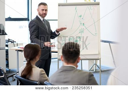 Portrait Of Bearded Business Coach Standing By Whiteboard Giving Presentation For Audience And Point