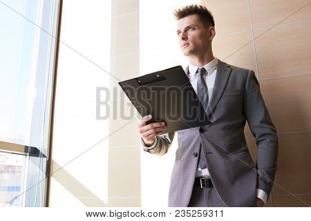Low Angle Portrait Of Ambitious Handsome Businessman Looking Away Holding Clipboard, Copy Space