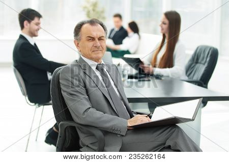 Senior Businessman With A Clipboard On The Background Of The Office.photo With Copy Space