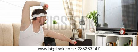 Young Handsome Man In Shorts And Vest Holds Pink Dumbbells In Hand. Watch Tv Lessons Single Combats