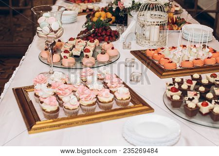 delicious candy,sweets,cupcakes,pops decorated with flowers on table at wedding reception. candy bar. tasty pink sweets for celebrations events and showers. luxury stylish catering poster