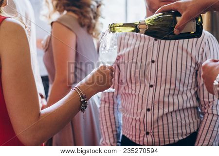 Waiter Pouring Champagne In Glass. Elegant People Holding Glasses Champagne At Luxury Wedding Recept