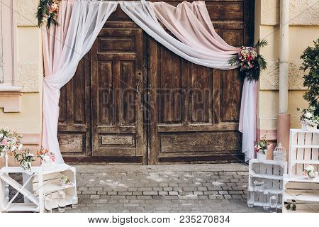 Rustic Wedding Photo Zone. Wooden Barn Doors With Fabric And White Boxes With Flowers And Candles At
