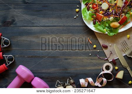 Fresh Healthy Salad With Dumbbells, Jump Rope, Tape Measure And Excercise Equipment On Wood Backgrou