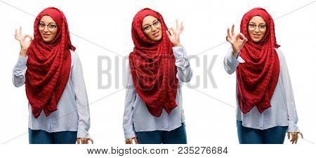Arab woman wearing hijab doing ok sign with hand, approve gesture isolated over white background