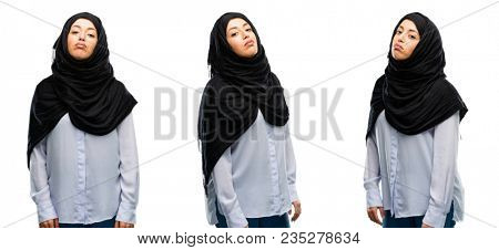 Arab woman wearing hijab with sleepy expression, being overworked and tired isolated over white background