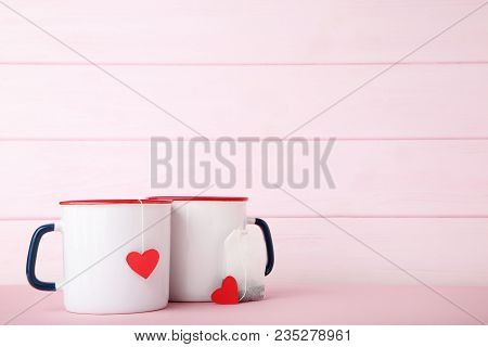 Mugs Of Tea With Red Heart And Teabag On Pink Background