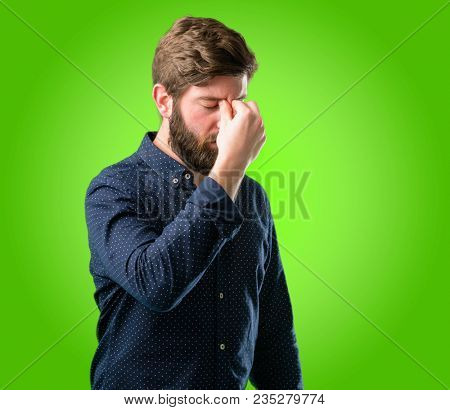 Young hipster man with big beard with sleepy expression, being overworked and tired, rubbes nose because of weariness over green background