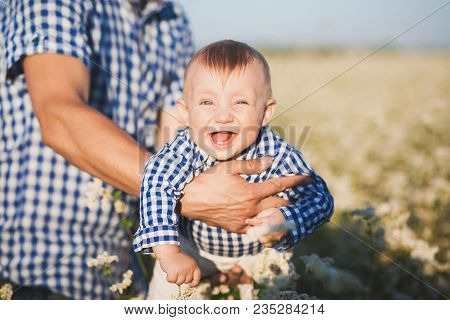Closeup Portrait Of Funny Happy Laughing Toothless Caucasian Baby In Hands Of Strong Daddy. Father T