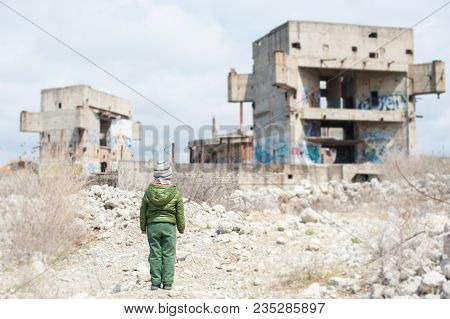 Little Boy In Jacket Stands Against Ruins Of Building As Result Of War Conflict